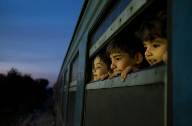 In the former Yugoslav Republic of Macedonia, three children look out of the window of a train, which was boarded by refugees primarily from Syria, Afghanistan and Iraq, at a reception centre for refugees and migrants, in Gevgelija. Credit: UNICEF/Ashley Gilbertson VII