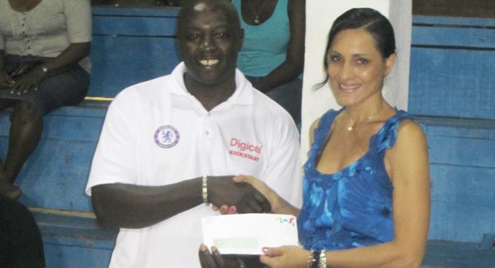 President Of Bequia Basketball And Tournament Co-Ordinator, Sabrina Mitchell, Receives Sponsorship Cheque From Digicel Representative, Gershom Dick.