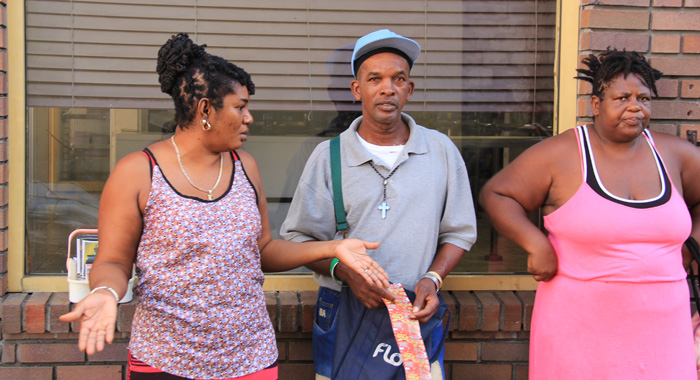 Davie Williams, Left, Discusses The Situation With Other Vendors. In Middle Street. (Iwn Photo)