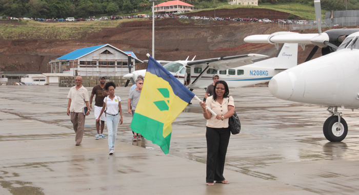 Director Of Airports, Corsel Robertson Waves An Svg Flag After Disembarking One Of The Four Aircraft At Argyle. (Iwn Photo)