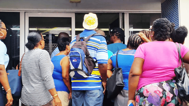 Persons Wait To Go Into Rbtt Bank On Wednesday. (Photo: Jerry S. George).