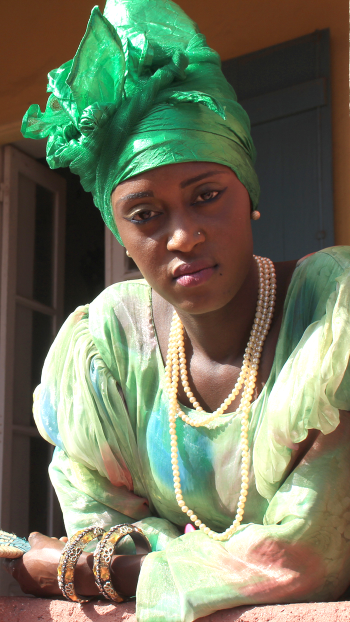 A Senegalese Woman, Dressed In Traditional Wear, Looks Out At Visitors To The Slave House On Gorée Island. (Iwn Photo)