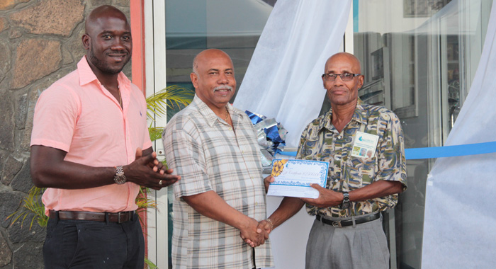 Sports Minister Cecil &Quot;Ces&Quot; Mckie, Centre, Presents The Award To Honouree Guy Lowe, Right, As Kevin Dickson, Chair Of Coreas Pharmacy Council Looks On. (Iwn Photo)