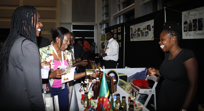 Dominican Entrepreneur, Kamarsha Sylvester, Owner Of Taste Of Eden, Right, Shares A Light Moment With Persons At Caribbean Week Of Agriculture 2016 Agriculture Marketplace In Grand Cayman On Oct. 26.