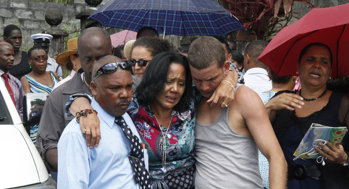 Detective Inspector Hezron Ballantyne And Another Man Help Israel Make Her Way To A Vehicle After She Saw Her Mother'S Body At The Scene. (Iwn Photo)