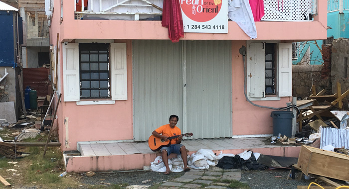 A Filipino Expat Plays His Guitar In Road Town Amidst Debris In The Aftermath Of Hurricane Irma. Cmc Photo