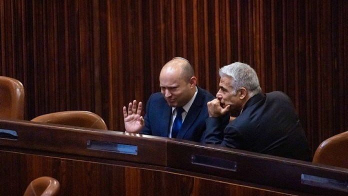 Yamina Party leader Naftali Bennett (left) and Yesh Atid Party head Yair Lapid in the Knesset plenum hall during the voting in the presidential elections, June 2, 2021. Photo by Olivier Fitoussi/Flash90.