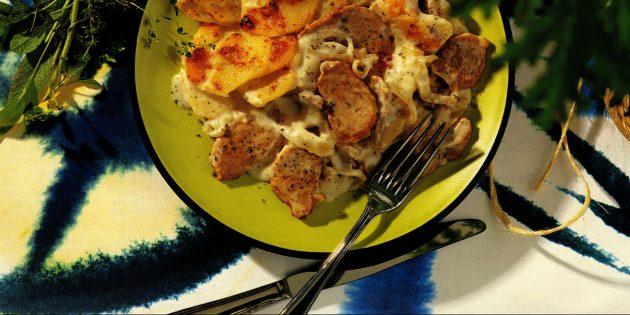 Thịt lợn với khoai tây và hành tây dưới nước sốt của Beamel trong lò nướng