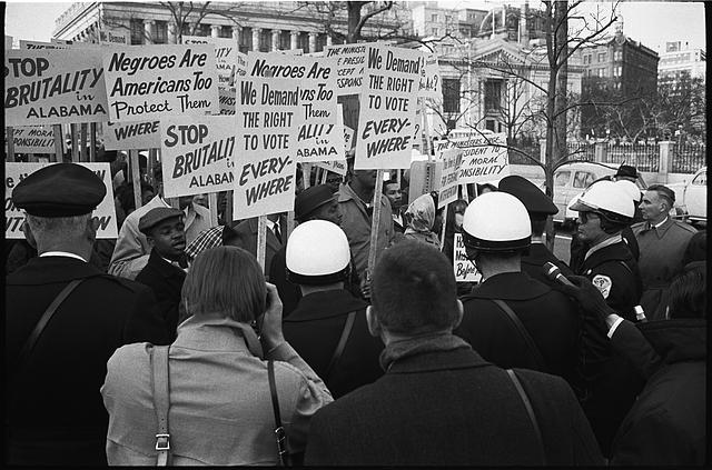 [African Americans demonstrating for voting rights in front of the White House as police and others watch; sign reads