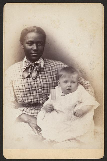 [Young African American woman holding a baby]