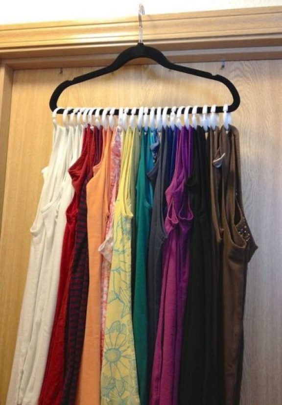 tank top storage hack: attach shower curtain rings to a hanger and hang it on top of a bedroom door