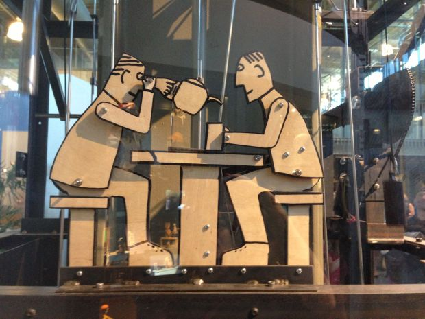 Close up of the clock's funny men drinking tea...
