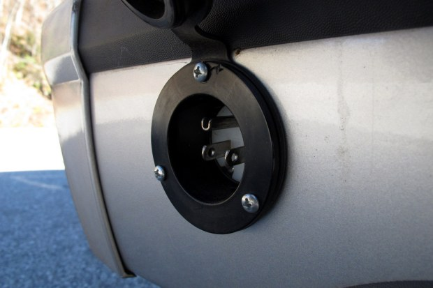 A rubber lid protects this exterior plug installed on the vehicle's rear bumper.