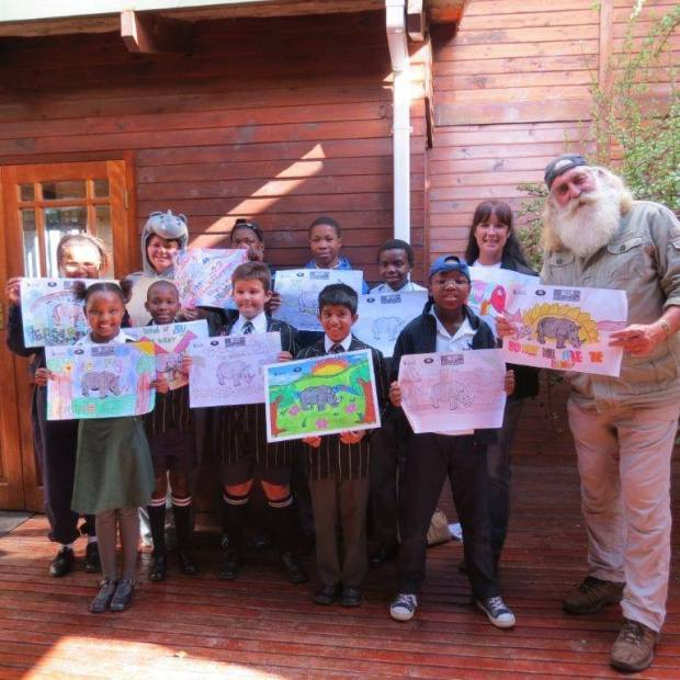 Africa's most colorful modern day explorers, Kingsley Holgate with children featuring their artwork against poaching.