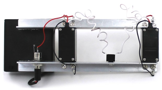 The lower rail is grounded through the power jack case contact and provides a common ground connection for the TRS jack and servos.  The upper rail is held at Vcc through the power jack center pin jumper wire, and carries drive current to both servos.