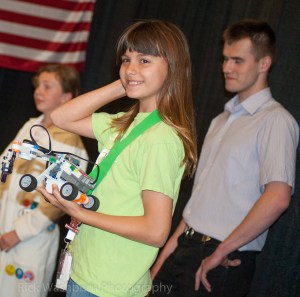 Young robot maker proud of her accomplishment.