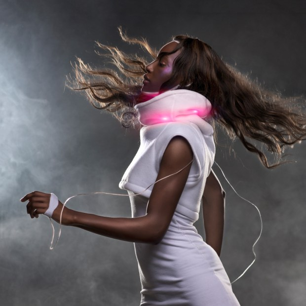 "Using galvanic sensors attached to the wearer's hands, the Mood Sweater reads excitement and translates into an ""external blush"" using color-changing LEDs in the collar. Photographed by Roger Dyckmans"