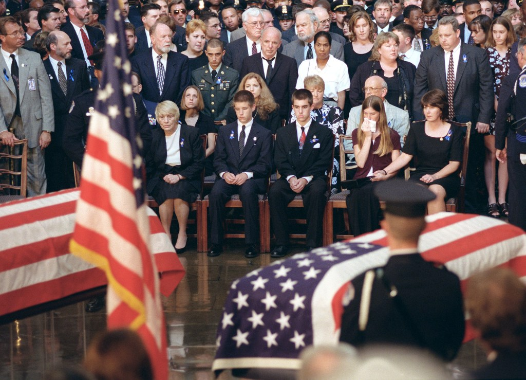 July 29, 1998: Evelyn Gibson, right, wife of slain U.S. Capitol Police Detective John Gibson, holds daughter Kristen's hand during a memorial service in the Rotunda for Gibson and Officer Jacob J. Chestnut, who were killed in a shooting at the Document Room entrance Friday. Sons Daniel and John are at left. (Scott J. Ferrell/CQ Roll Call)