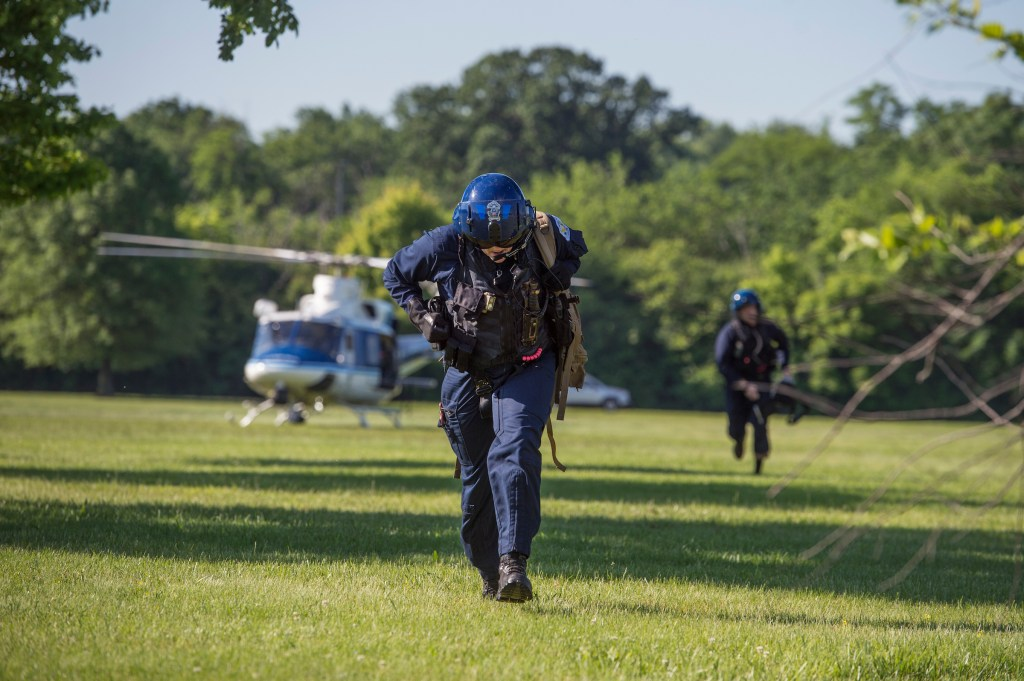 UNITED STATES - MAY 17: Medical personnel rush to treat a fallen runner during the ACLI Capital Challenge 3 Mile Team Race in Anacostia Park, May 17, 2017. The runner was flown out via helicopter. (Photo By Tom Williams/CQ Roll Call)