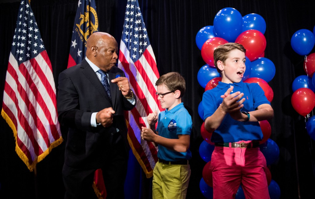 Democratic Rep. John Lewis of Georgia dances on stage before speaking at Ossoff's rally on Tuesday night. (Bill Clark/CQ Roll Call)