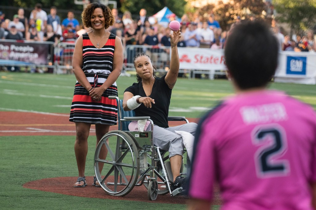 Capitol Police officer Crystal Griner throws out the first pitch in the Congressional Women's Softball game that pits congresswomen against female journalists at Watkins Recreation Center on Capitol Hill on Wednesday. Griner was injured in last week's shooting at the Republican baseball practice. The game benefits the Young Survival Coalition that helps young women with breast cancer. (Tom Williams/CQ Roll Call)