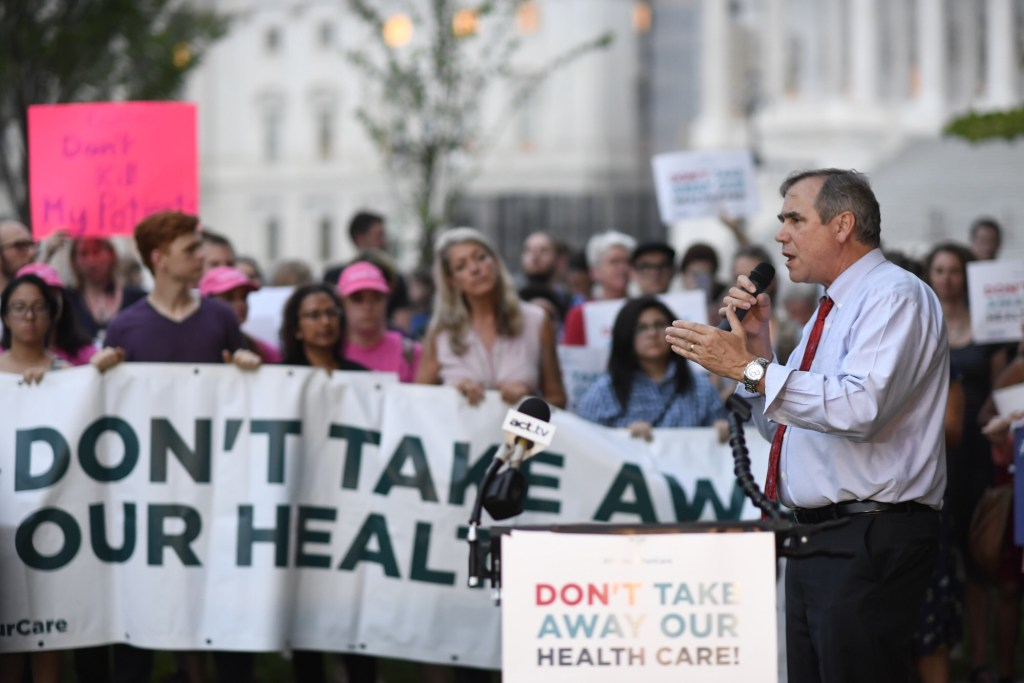 Sen. Jeff Merkley, D-Ore., speaking to dozens of health care protesters outside Capitol. (Bill Clark/CQ Roll Call)