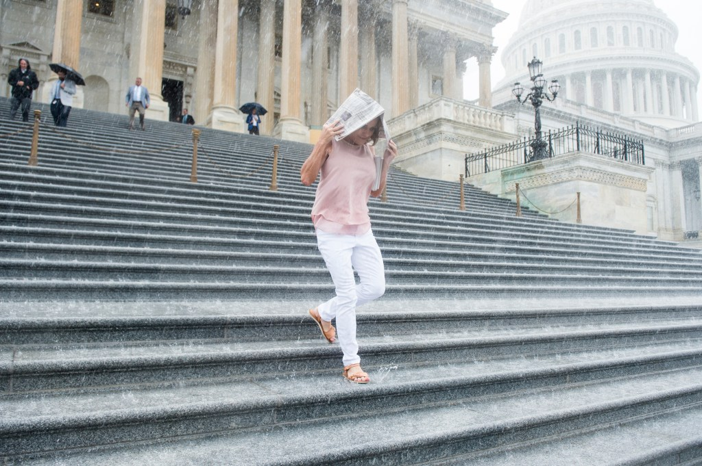 UNITED STATES - JULY 28: Rep. Lynn Jenkins, R-Kan., covers herself with a newspaper as she runs down the House steps in the pouring rain following the final votes as Congress leaves town for their summer recess on Friday, July 28, 2017. (Photo By Bill Clark/CQ Roll Call)