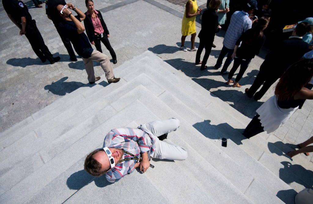 UNITED STATES - AUGUST 21: Staffers sit on the Senate steps in front of the U.S. Capitol during the partial solar eclipse on Monday, Aug. 21, 2017. (Photo By Bill Clark/CQ Roll Call)