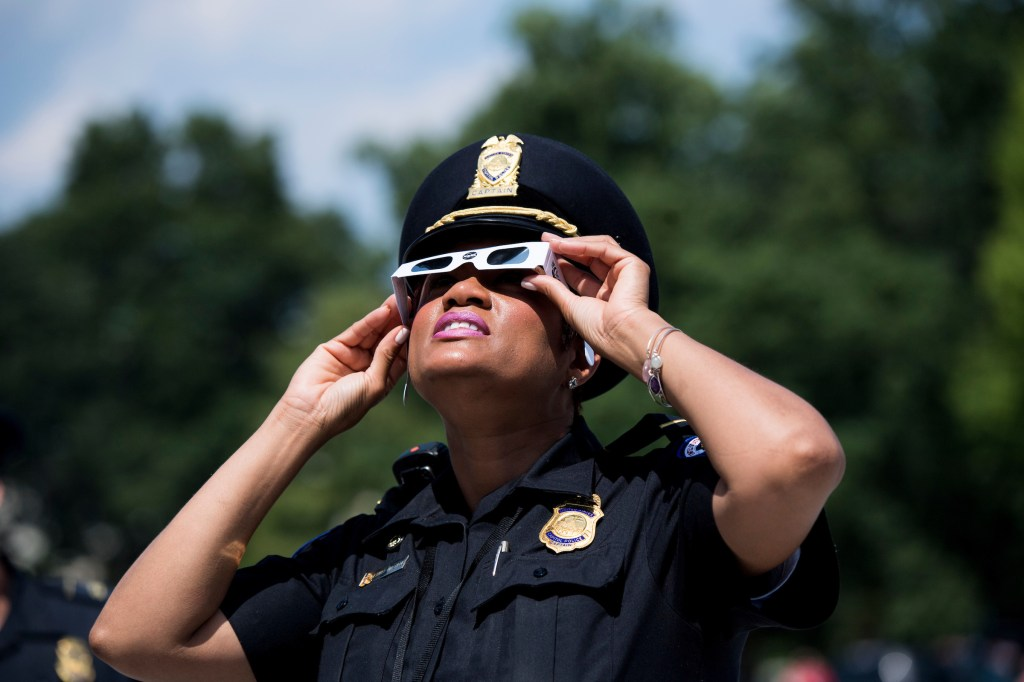 UNITED STATES - AUGUST 21: U.S. Capitol Police took a moment to check out the on the partial solar eclipse on the Senate steps in front of the U.S. Capitol on Monday, Aug. 21, 2017. (Photo By Bill Clark/CQ Roll Call)