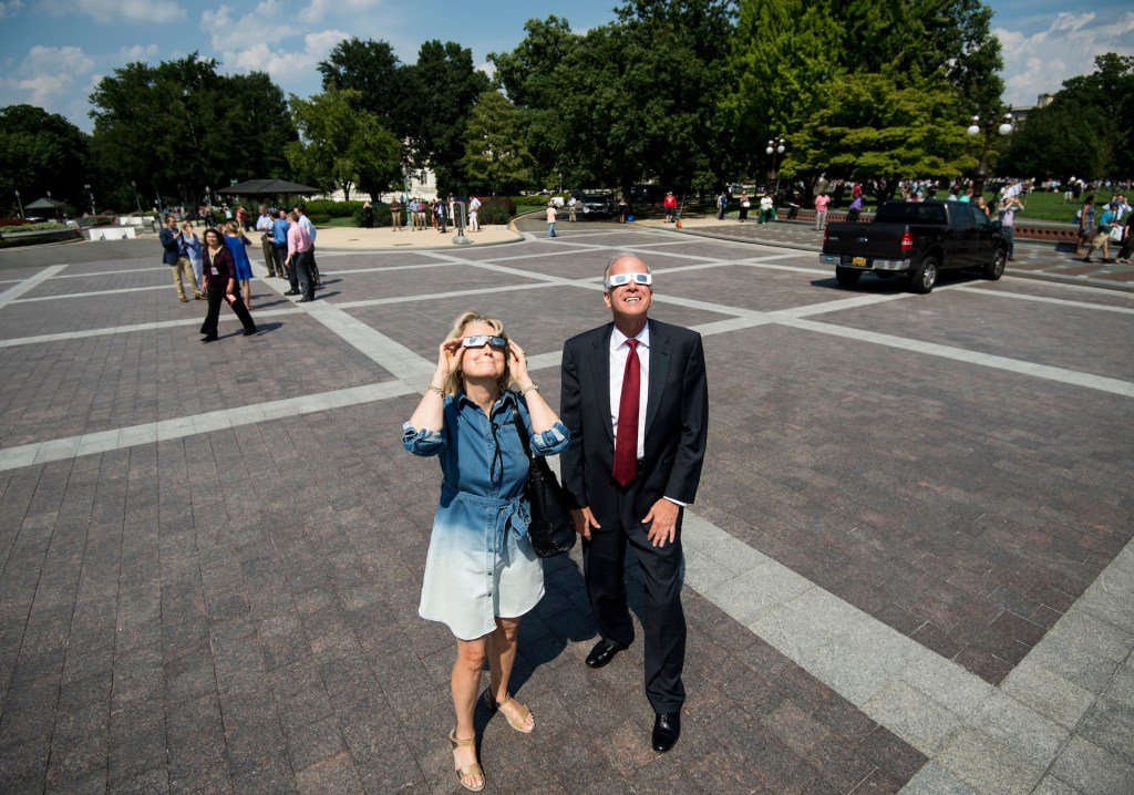 UNITED STATES - AUGUST 21: Sen. Jerry Moran, R-Kan., along with Bloomberg/BNA's Nancy Ognanovich, look up at the partial solar eclipse on the east plaza of the U.S. Capitol on Monday, Aug. 21, 2017. (Photo By Bill Clark/CQ Roll Call)