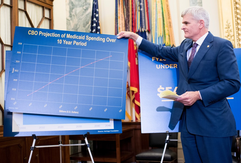 UNITED STATES - SEPTEMBER 13: Sen. Bill Cassidy, R-La., helps swap out posters during the news conference to discuss block grant funding for healthcare on Wednesday, Sept. 13, 2017. (Photo By Bill Clark/CQ Roll Call)