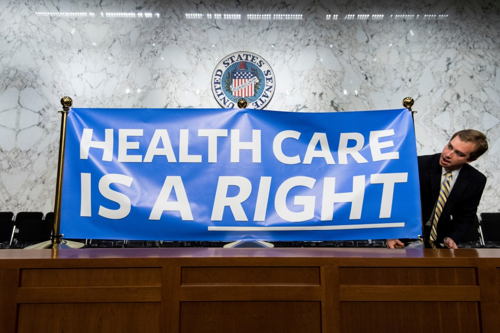 Staffers set up signs for Sen. Bernie Sanders' event to introduce the Medicare for All Act of 2017 on Wednesday. (Bill Clark/CQ Roll Call)