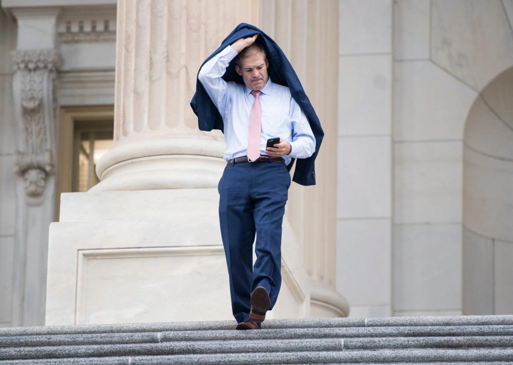 UNITED STATES - OCTOBER 11: Rep. Jim Jordan, R-Ohio, holds his jacket over his head as he walks down the House steps in a light rain following a vote on Wednesday, Oct. 11, 2017. (Photo By Bill Clark/CQ Roll Call)