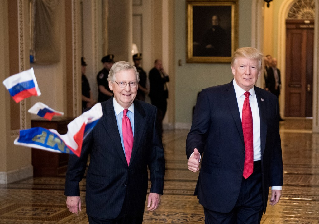 President Donald Trump and Majority Leader Mitch McConnell walk to the majority leader's office on Oct. 24, 2017. A protester threw Russian flags and shouted as they walked by. (Bill Clark/CQ Roll Call)