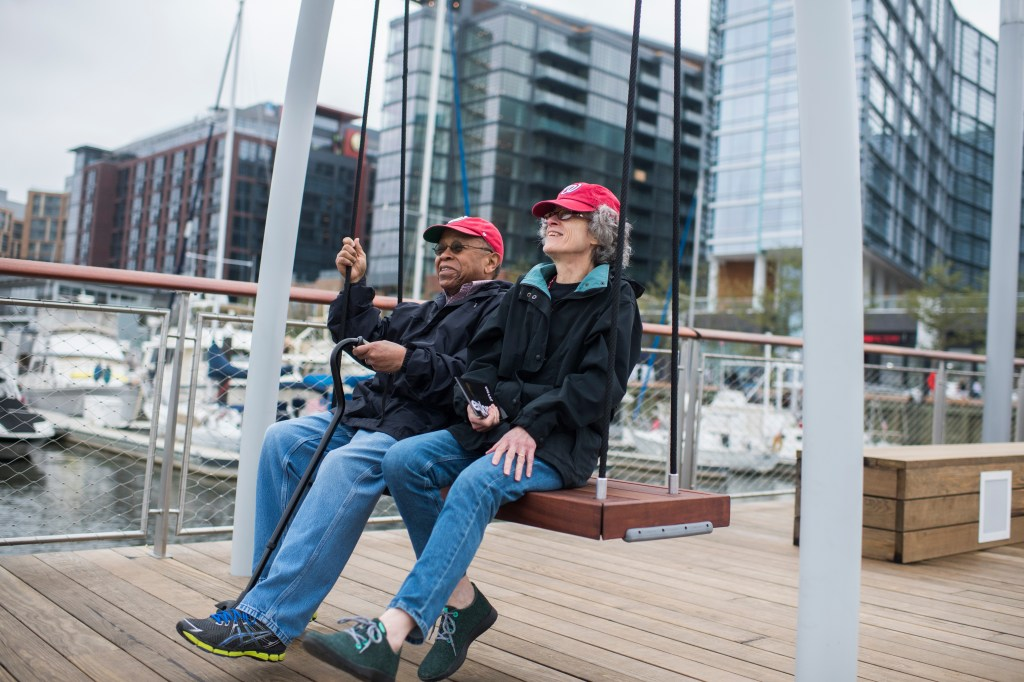 UNITED STATES - OCTOBER 12: B.J. Forman, right, and Larry Goffney, of Alexandria, Va., relax on a swing during the opening ceremony of the Wharf complex along Maine Avenue, SW, on October 12, 2017. (Photo By Tom Williams/CQ Roll Call)