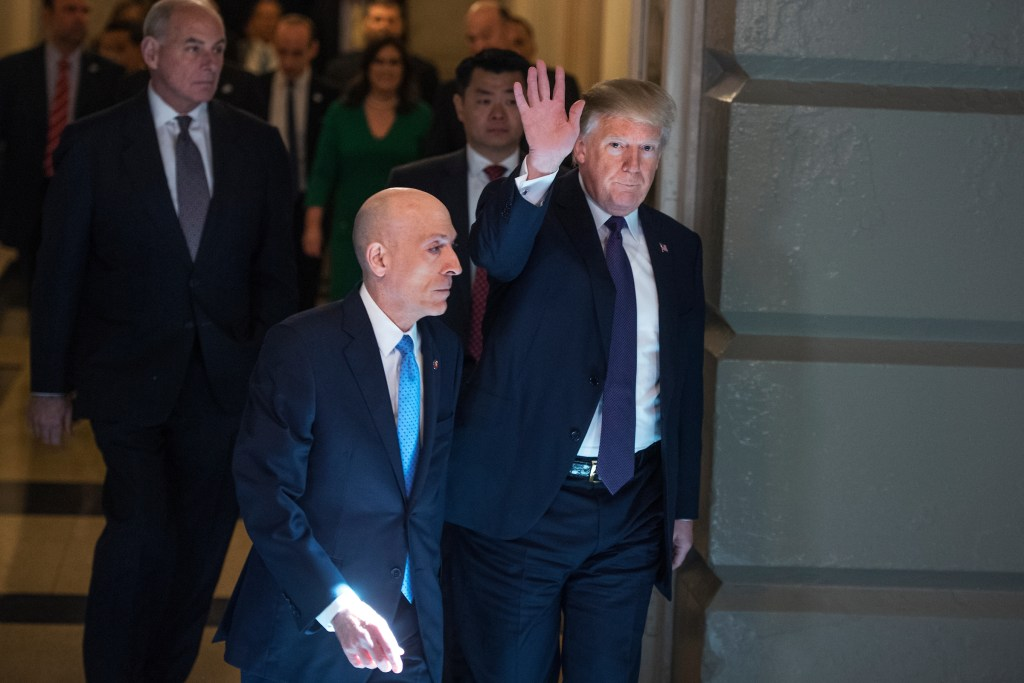 President Donald Trump arrives for meeting with the House Republican Conference in the Capitol to discuss the GOP's tax overhaul bill. White House Chief of Staff John Kelly, far left, and House Sergeant at Arms Paul Irving, foreground, also appear. (Tom Williams/CQ Roll Call)