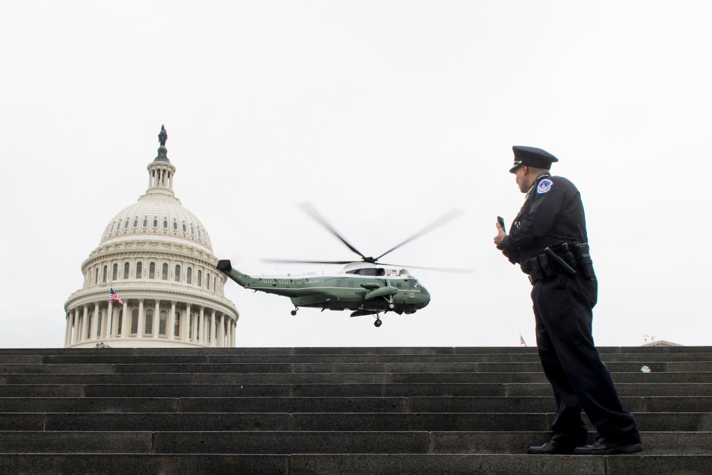 UNITED STATES - JANUARY 20: A U.S. Capitol Police officer takes a photo as a Marine helicopter carrying former President Barack Obama and former First Lady Michelle Obama lifts off from the East Plaza of the U.S. Capitol following the swearing in of Donald Trump as the 45th President of the United States on Friday, Jan. 20, 2017.(Photo By Bill Clark/CQ Roll Call)