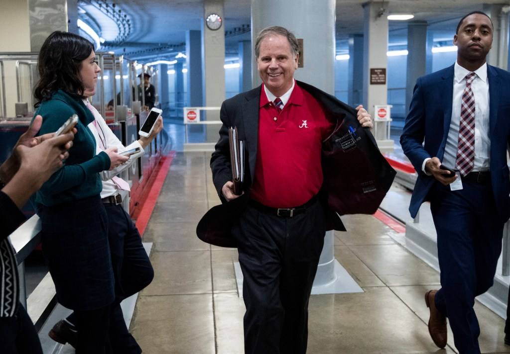 UNITED STATES - JANUARY 9: Sen. Doug Jones, D-Ala., flashes his University of Alabama shirt as he arrives in the Capitol on Tuesday, Jan. 9, 2018. Alabama defeated the University of Georgia for the NCAA football championship. (Photo By Bill Clark/CQ Roll Call)