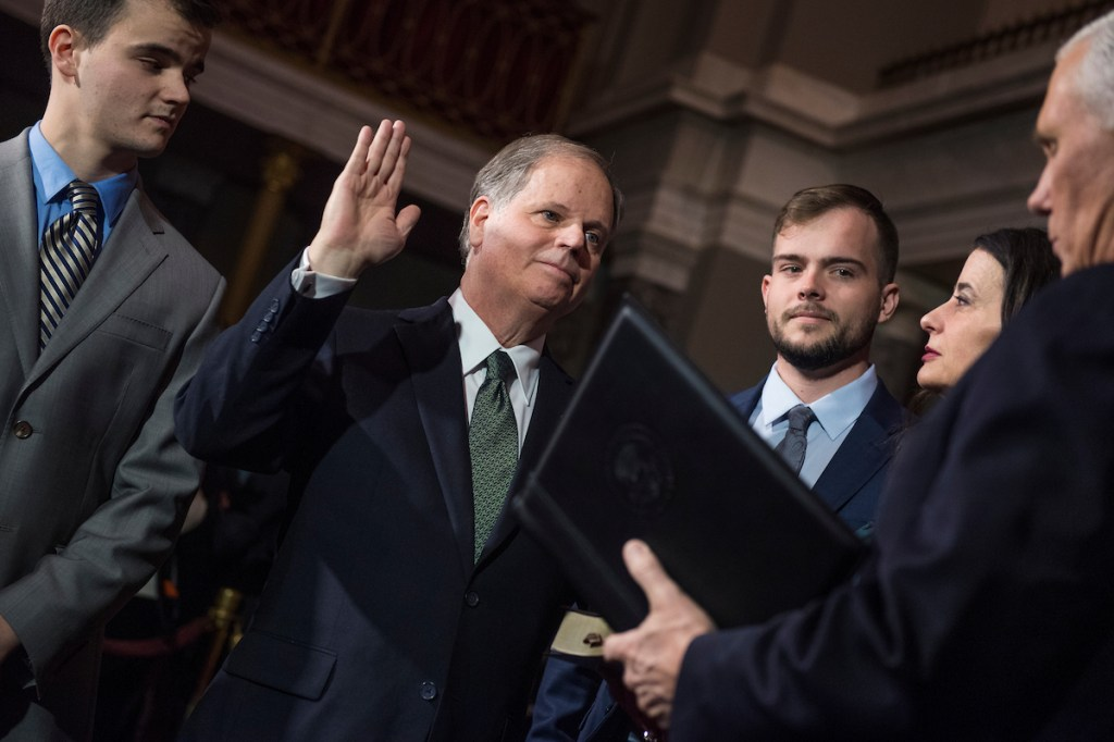 UNITED STATES - JANUARY 03: Sen. Doug Jones, D-Ala., is administered an oath by Vice President Mike Pence during a swearing-in ceremony in the Capitol's Old Senate Chamber after the actual event on the senate floor on January 3, 2018. Jones' wife Louise, and sons Chris, left, and Carson, also appear. (Photo By Tom Williams/CQ Roll Call)