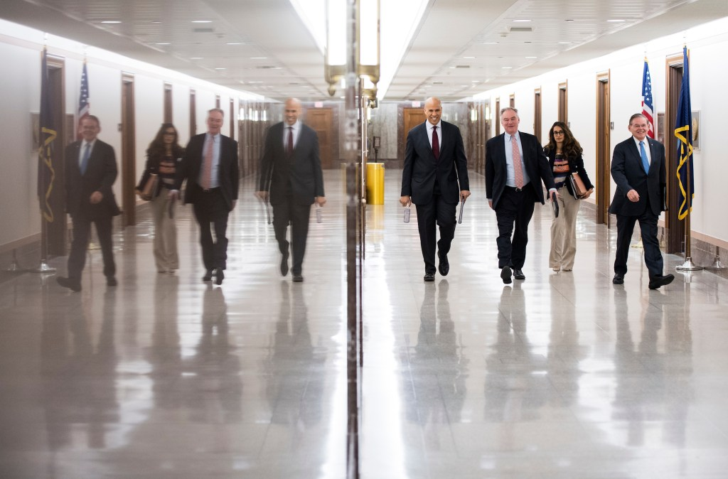 UNITED STATES - FEBRUARY 6: From left, Sen. Cory Booker, D-N.J., Sen. Tim Kaine, D-Va., and Sen. Bob Menendez, D-N.J., walk to their morning committee hearing in the Dirksen Senate Office Building on Tuesday, Feb. 6, 2018. (Photo By Bill Clark/CQ Roll Call)