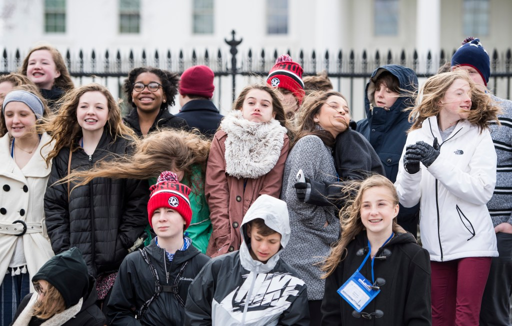 A group of students with the Washington Workshops program brace against a gust of wind as they pose for a group photo in front of the White House during the high winds warning in Washington on Friday. (Bill Clark/CQ Roll Call)