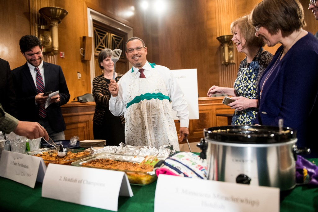 UNITED STATES - APRIL 25: Rep. Keith Ellison, D-Minn., wears a apron while holding a spatula during the eighth annual Minnesota Congressional Delegation Hotdish Competition in the Dirksen Senate Office Building on Wednesday, April 25, 2018. (Photo By Bill Clark/CQ Roll Call)