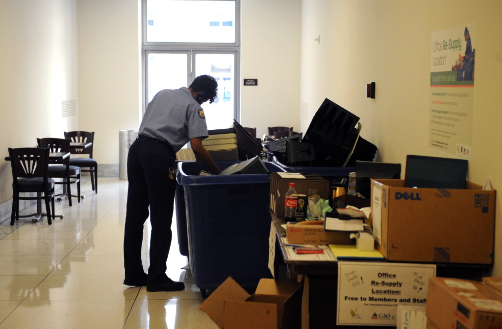 An Architect of the Capitol employee goes through supplies that are up for grabs at a drop site for discarded items from the office moving process, December 03, 2008.