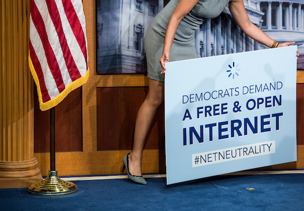 UNITED STATES - MAY 16: A staffer removes a 'net neutrality' sign after a press conference following the vote that would help stop the Federal Communications Commission's effort to reverse Obama-era regulations on net neutrality May 16, 2018. (Photo By Sarah Silbiger/CQ Roll Call)