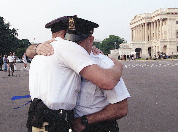 7-28-98.U.S. CAPITOL-- U.S. Capitol Police officer T.J. Wissemann hugs fellow officer S.I. Flax to console him.Flax had become emotional after the bodies of U.S. Capitol Police officers John Gibson and Jacob J. Chestnut who were slain while guarding the Capitol arrived to lay in state in the Rotunda. .CONGRESSIONAL QUARTERLY PHOTO BY DOUGLAS GRAHAM
