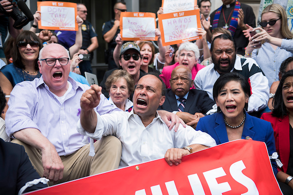 UNITED STATES - JUNE 13: From left, Reps. Joe Crowley, D-N.Y., Jan Schakowsky, D-Ill., actor John Cusack, Luis Gutierrez, R-Ill., John Lewis, D-Ga., Al Green, D-Texas, Judy Chu, D-Calif., Pramila Jayapal, D-Wash., and others sit on the 14th Street NW, entrance to the U.S. Customs and Border Protection in protest of the Trump Administration's policy of separating parents and children at the border on June 13, 2018. (Photo By Tom Williams/CQ Roll Call)