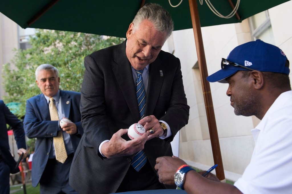 UNITED STATES - JULY 18: Rep. Peter King, R-N.Y., gets his baseball signed by Hall of Fame member Tim Raines, during the American Meat Institute's annual Hot Dog Lunch in the Rayburn courtyard on July 18, 2018. Rep. Brad Wenstrup, R-Ohio, also appears. (Photo By Tom Williams/CQ Roll Call)
