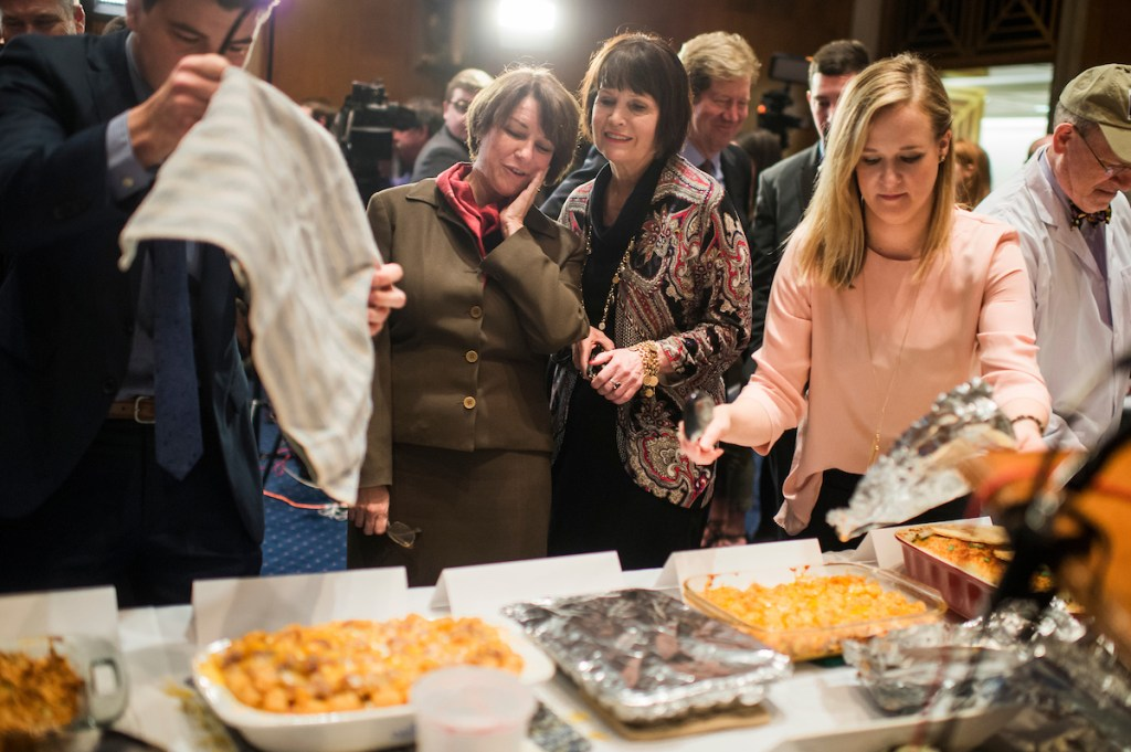 Sen. Amy Klobuchar, D-Minn., left, and Betty McCollum, D-Minn., confer during the annual Minnesota Congressional Delegation Hotdish Competition in Dirksen Building, March 8, 2017. (Photo By Tom Williams/CQ Roll Call)