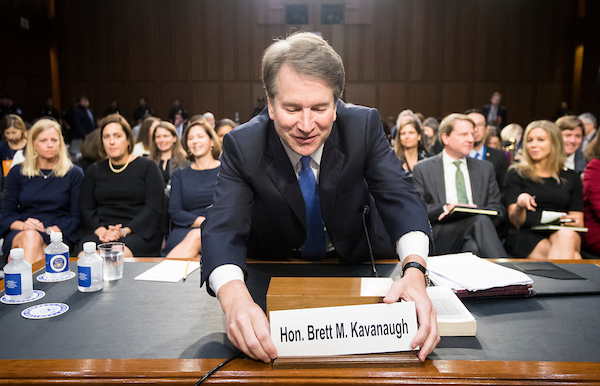 UNITED STATES - SEPTEMBER 6: Brett Kavanaugh adjusts his nameplate as he takes his seat for day three of his confirmation hearing in the Senate Judiciary Committee to be Associate Justice of the Supreme Court on Thursday morning, Sept. 6, 2018. (Photo By Bill Clark/CQ Roll Call)