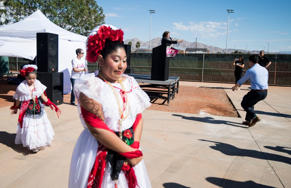Sen. Catherine Cortez Masto, D-Nev., speaks on stage as dancers with the Mexico Vivo group prepares to perform at the East Las Vegas Community Center, an early voting location, in Las Vegas on Saturday, Oct. 20, 2018, the first day of early voting in Nevada. (Photo By Bill Clark/CQ Roll Call)